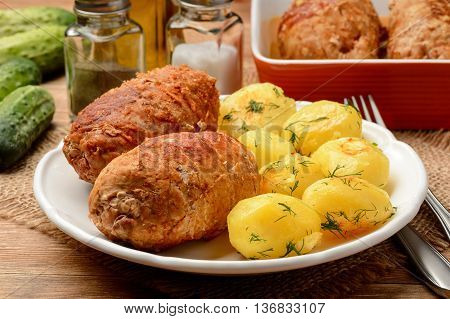 Roasted meat roulades sereved  with baked potatoes. On wooden background.