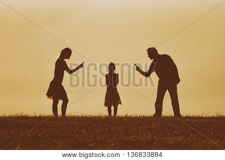 Silhouette of a angry mother and father scolding their daughter.