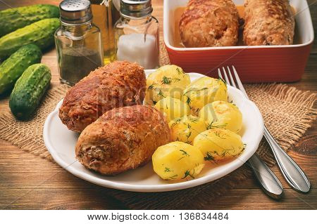 Roasted meat roulades served  with baked potatoes. On wooden background.