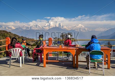 GOREPANI NEPAL - APRIL 10 2016 : Trekkers chill out and see Dhaulagiri mountain from viewpoint at Gorepani village, Annapurana loop trekking route Nepal.
