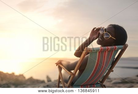 Fashionable woman sitting at the beach