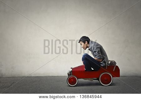 Teenager driving a toy car