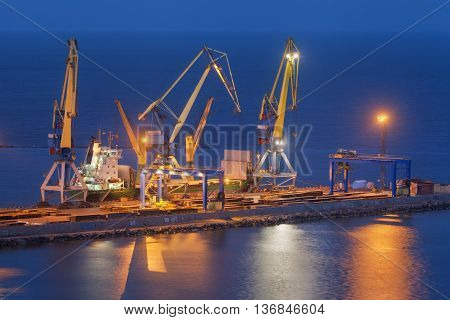 Cargo freight ship with working cranes bridge in sea port at twilight. Sea commercial port at night in Mariupol Ukraine. Industrial view. Cargo port logistic