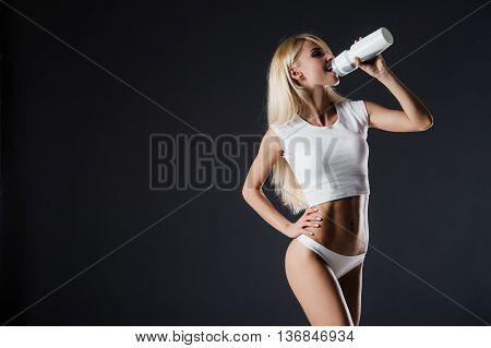 healthy young sexy woman with perfect fitness body and glutes drinking water against a black background.