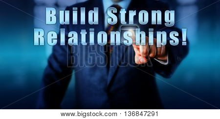 Businessman is touching the phrase Build Strong Relationships! on a virtual monitor. Motivational appeal business concept and call to action. Close up torso shot facing frontally. Blurred background.