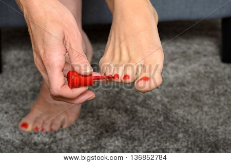 Woman Applying Red Nail Varnish