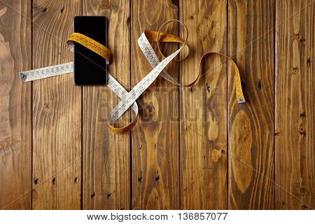 Smartphone tied in tailoring meter presented on rustic wooden table top view