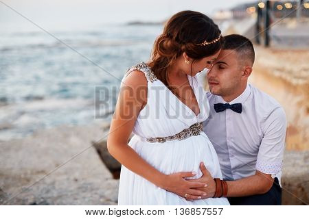 young mid adulted happy love couple of male and female standing on blue sea beach on summertime in vacations holding embracing eachother expecting baby soon