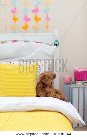 Primer plano de dormitorio infantil con un oso de peluche en la cama