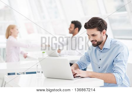 I can handle any task. Handsome businessman working in modern office and looking at laptop with colleagues in background