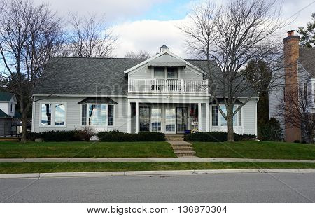 HARBOR SPRINGS, MICHIGAN / UNITED STATES - DECEMBER 25, 2015: An East Bluff Drive home, with a balcony and a view of Little Traverse Bay, in Harbor Springs, Michigan.