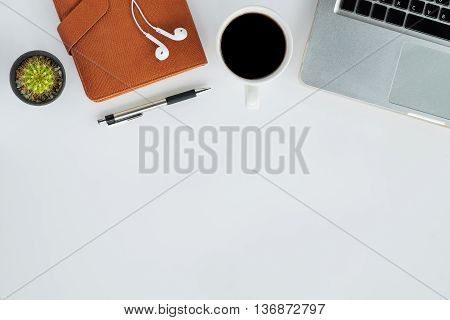 Top view of white office desk table with laptop leather notebook pen headphone and cup of coffee.Office gadgets with copy space