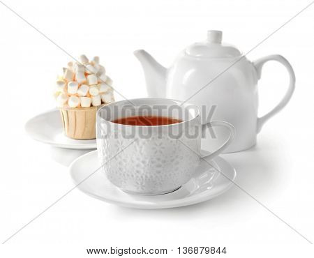 Cup of tea with tasty cupcake and teapot, isolated on white