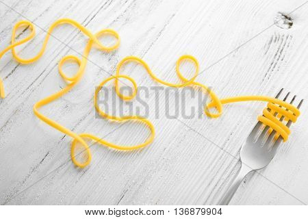 Swirls of pasta and fork on wooden background