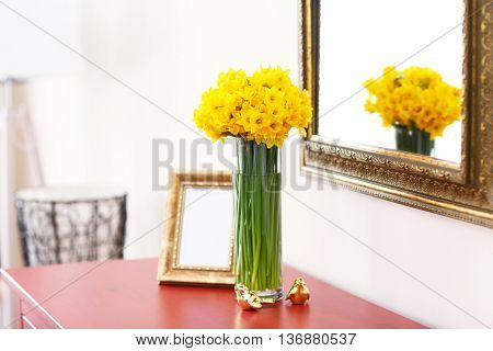Beautiful bouquet of yellow narcissus on chest of drawers