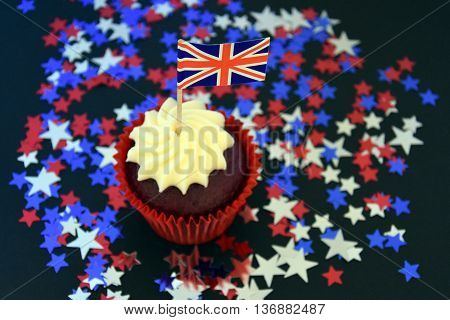 UK celebration cake party food with red white and blue cupcake and british flag. Celebration patriotism and holidays concept - close up of glazed muffin decorated with british flag