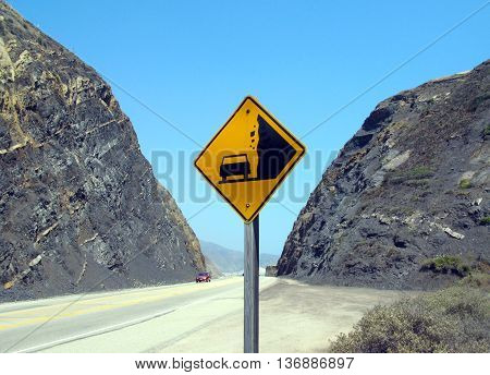 Sign warns of rockslide before canyon on pacific coast highway near Malibu, California