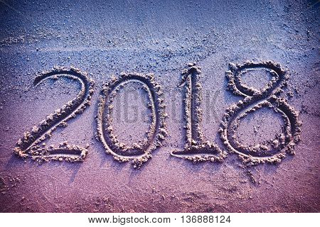 Year 2018 handwritten on seashore sand. Concept of upcoming new year and passing of time. Vintage tone.
