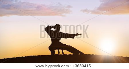 Fighter performing karate stance against clouds