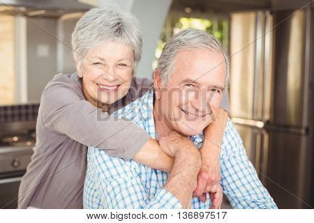 Portrait of cheerful senior couple embracing in kitchen at home