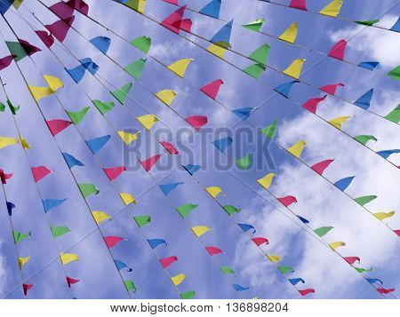 Lines on multicolored bunting in blue cloudy sky