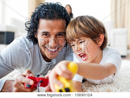 Excited little boy and his father playing video games lying on the floor in the living-room