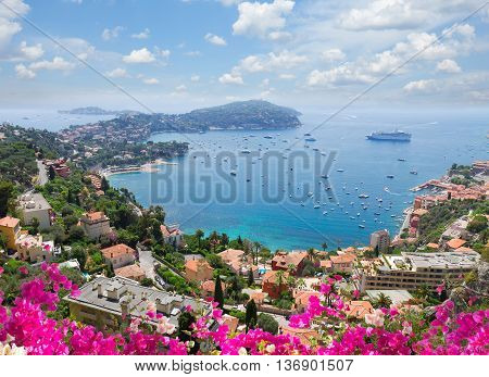 lanscape of riviera coast, turquiose water, flowers and blue sky of cote dAzur at summer day, France