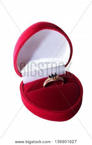 Gold ring with sapphires in a red velvet box on a white background.