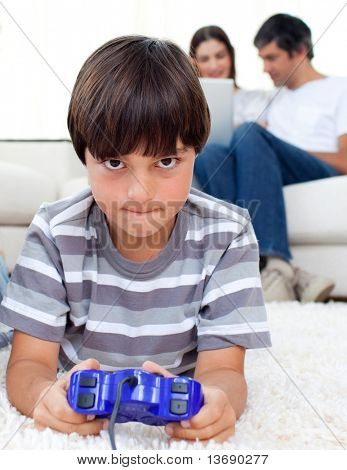 Pensive boy playing video games lying on a floor