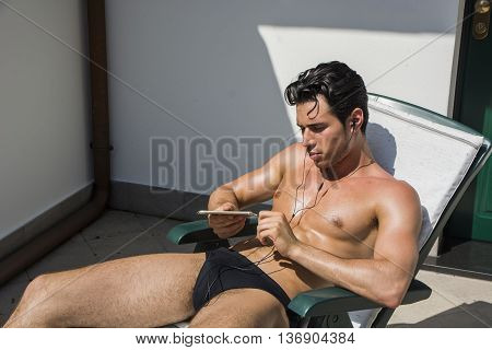 Shirtless Young Man Drying Off in Hot Sun Listening to Music Through Earphones, Muscular Man Wearing Bathing Suit Sunbathing on Beach Lounge Chair, Eyes Closed
