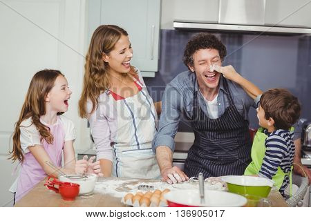 Happy family enjoying while cooking food in kitchen at home