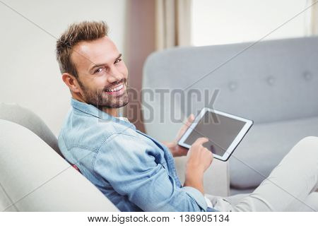 Portrait of young man smiling while using digital tablet on sofa at home