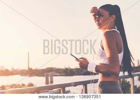 Sporty woman. Beautiful young woman in headphones holding her smart phone and looking away while standing on the bridge with urban view in the background