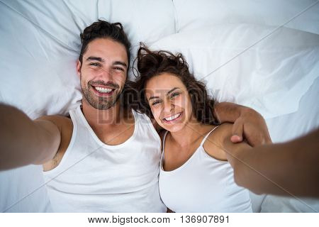 High angle view of couple taking self portrait on bed at home