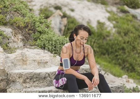 Runner woman resting after long run on the beach. Beautiful vivacious woman jogging on the beach with cloudy weather