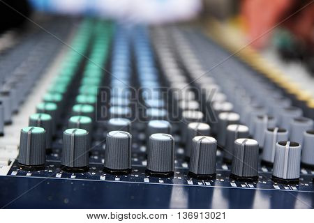 Part of a professional sound mixing console studio music device for audio signals with controlling knobs