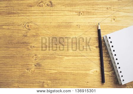 Top view of wooden desktop with blank spiral notepad and pencil. Mock up