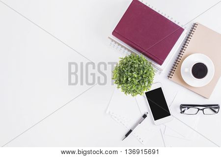White office desktop with blank cellular phone glasses coffee cup spiral notepads book decorative plant and other items. Top view Closeup Mock up