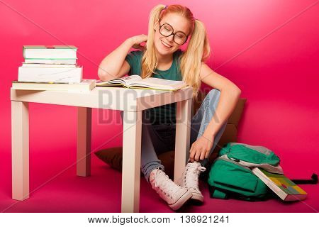 Dreamy Schoolgirl With Hairstyle As Pippi Longstocking And Big Eyeglasses Sitting Behind The Table F