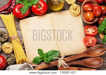 Italian food cooking. Tomatoes, basil, spaghetti pasta, olive oil and cookbook for your recipe on wooden kitchen table. Top view with copy space