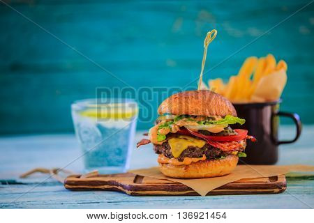 Tasty street food grilled beef burger in crispy shortbread with lettuce and mayonnaise accompanied with french fries and lemonade served on small cutting board a rustic wooden table with copy space.