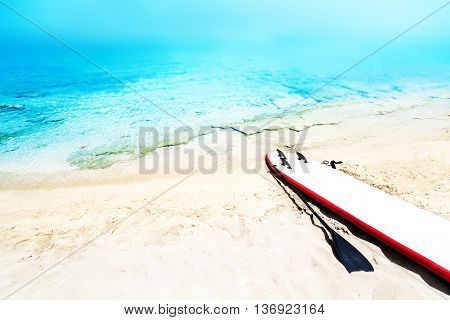 Holiday beach sunny seascape with surf board sand and ocean. Summer vacation concept