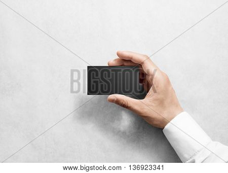 Hand hold blank plain black business card design mockup. Clear namecard mock up template holding arm. Visit pasteboard paper surface display front. Check small offset card print. Business branding