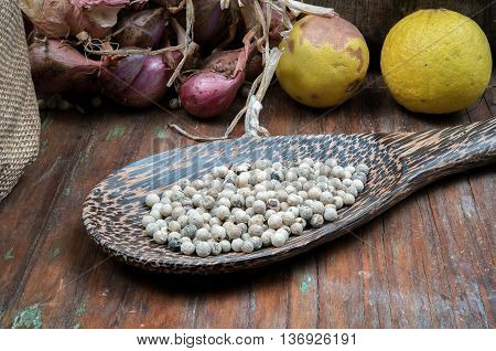 spices with pepper in ladle on dark wooden table