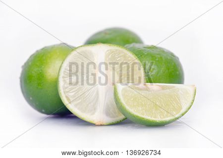 Lemon fruit (Other names are lime in French citrus fruit lime green Key lime Persian lime Kaffir lime desert lime) with half cross section and partial section isolated on wooden board