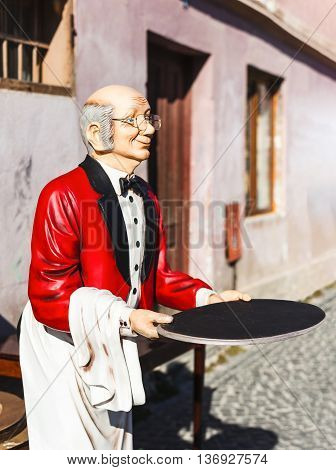 butler man statue with red jacket and tray