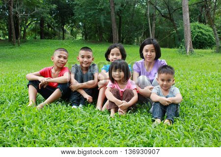 Six asian kids having a good time in the park, spring time.