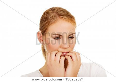Stressed young woman biting nails