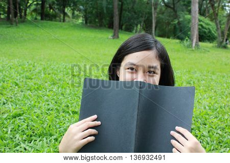 Young girl reading the book in the park, spring time.