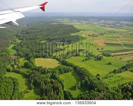 Typical german landscape forest and fields - aerial view from plane with visible wing during landing approach